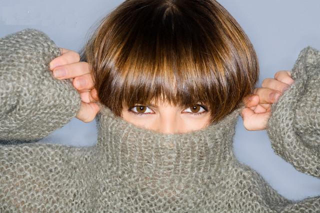 Close-up of a young woman, covering her face in turtleneck --- Image by © Glowimages/Corbis